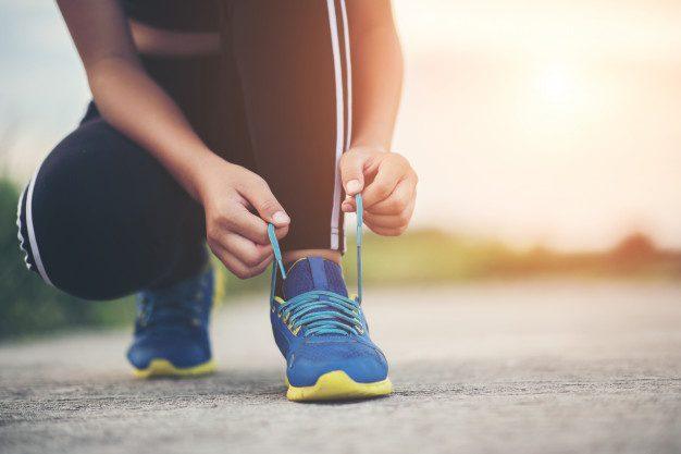 corredora se prepara para o aquecimento antes de correr amarrando os tênis