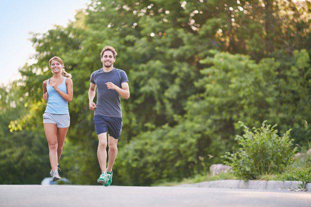 Como começar a correr? Casal correndo em meio à natureza